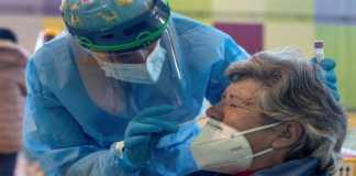 Una mujer se coloca el cubrebocas