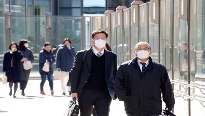 Caminantes en Japón protegiéndose de la nueva cepa