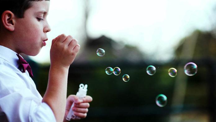 Niño lanza burbujas