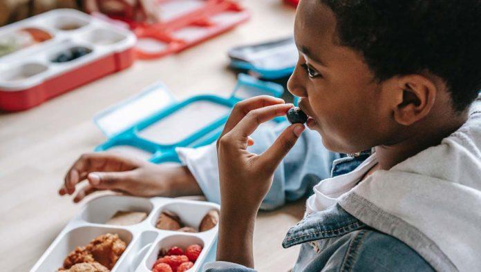 Niño comiendo alimentos para mejorar el sistema inmune